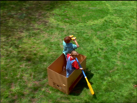 high angle 2 boys in large box playing sailors outdoors / 1 using binoculars while other steers with oar - cardboard box stock videos & royalty-free footage
