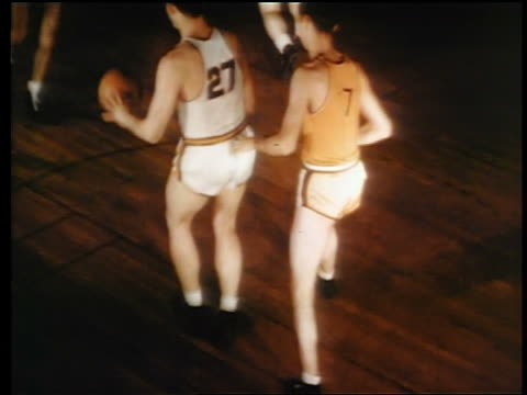 1945 high angle pan 2 teams playing basketball / one man makes basket / industrial - shooting baskets stock videos & royalty-free footage