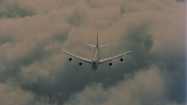 aerial high angle 747 jet flying over cloud level + water at high speed - air to air shot stock videos and b-roll footage