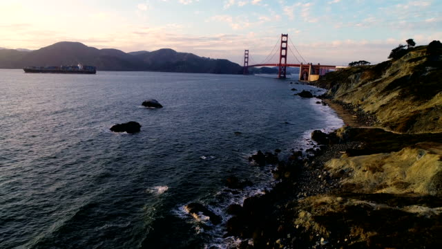 high angle above bakers beach in san francisco with golden gate bridge and cargo ship leaving bay area - baia di san francisco video stock e b–roll