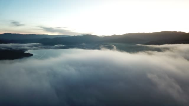 high angle aerial panoramic view of lugu lake above the clouds in china at sunrise - us navy stock videos & royalty-free footage