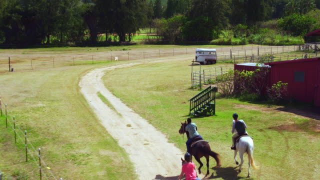 vidéos et rushes de high angle aerial shot of three people racing around a corner on horses - trois personnes