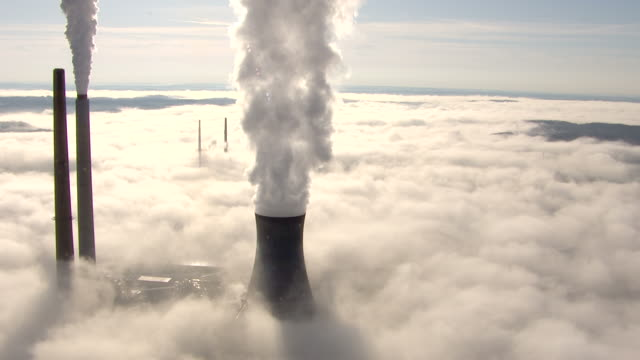 high angle aerial , smoke rises above a fog bank at a coal,fired power plant. / west virginia - schornstein konstruktion stock-videos und b-roll-filmmaterial