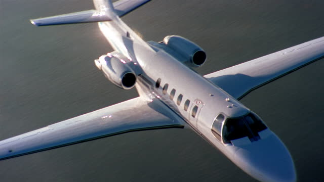 high angle aerial tracking shot jet flying over water and clouds - corporate jet stock videos & royalty-free footage
