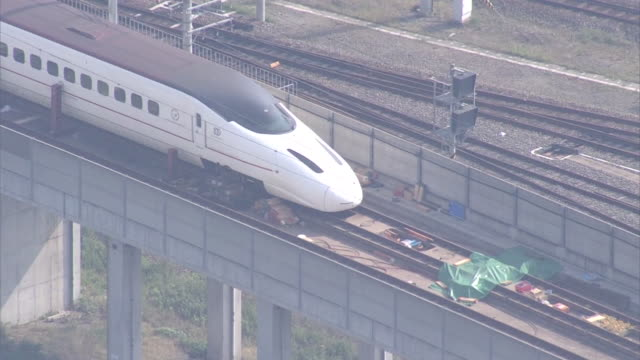 high angle aerial view of a derailed kyushu shinkansen bullet train stopped near kumamoto station after consecutive earthquake hits during 2016... - kyushu shinkansen stock videos and b-roll footage