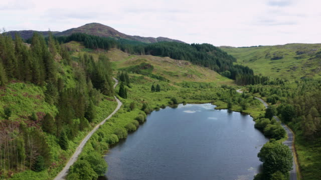 high angle aerial view of a small scottish loch in south west scotland on a summer morning - galloway scotland stock videos & royalty-free footage