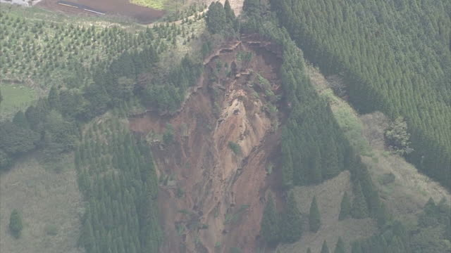 high angle aerial view of landslide caused by consecutive earthquake attacks in kumamoto, debris buring the houses at the foot of the mountain,... - 地震点の映像素材/bロール