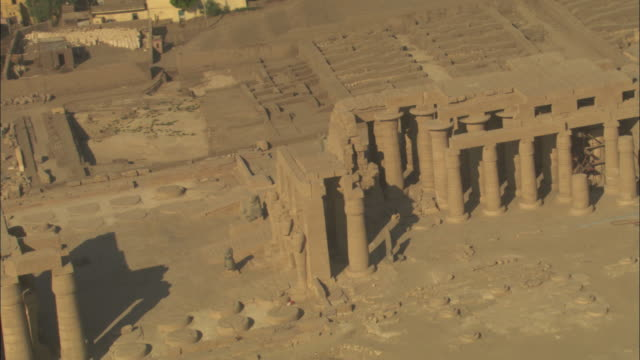high angle, aerial zoom-out - sandstone historical ruins with large pillars stand out in the egyptian nile delta - sandstone stock videos & royalty-free footage