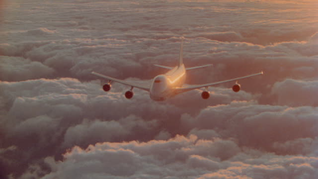 AERIAL high angle aircraft point of view around 747 jet flying over sea of orange clouds at sunset/rise