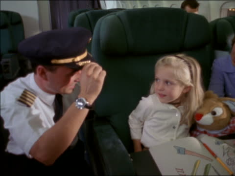 high angle airline pilot putting hat on little girl on airplane