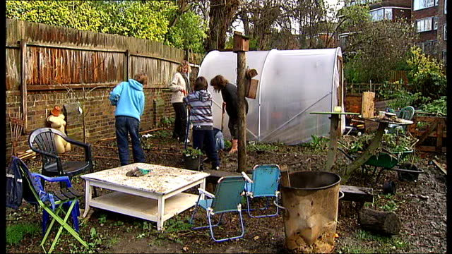 high angle angle view of plot of land now cultivated as allotments poly tunnel in middle of allotment block of flats which overlook allotment pan to... - gemeinschaftsgarten stock-videos und b-roll-filmmaterial