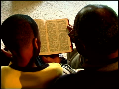 vídeos de stock, filmes e b-roll de high angle arc looking down to a grandfather and grandson reading the bible together. - bíblia