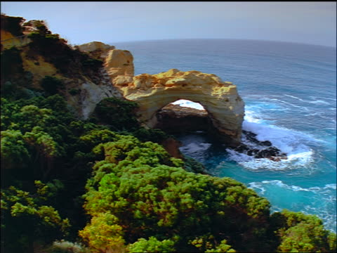 high angle arched rock formation on coastline / great ocean road, victoria, australia - port campbell national park stock videos & royalty-free footage