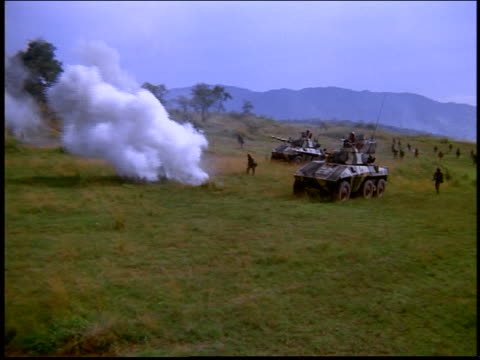 high angle Army soldiers with tanks moving through field with explosions / Rio de Janeiro, Brazil