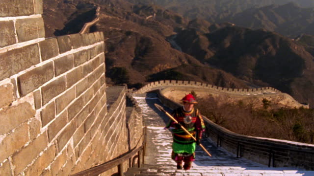 high angle asian guard in traditional dress walking on great wall of china with mountains in background / china - army点の映像素材/bロール