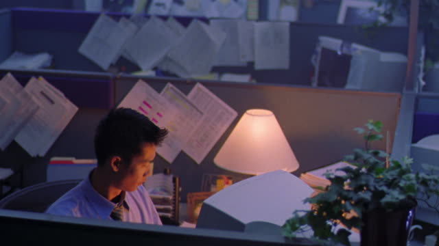 high angle Asian man works at computer + drinks coffee in cubicle with lamp on / other cubicles in dark in background
