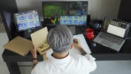 high angle asian matured chinese man with gray hair eating take out food while working at home with stock exchange market multiple computer monitor monitoring market trend