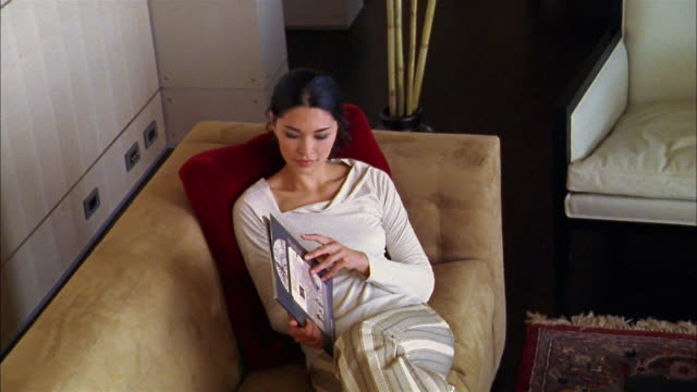 vídeos de stock e filmes b-roll de high angle asian woman sitting against pillow on sofa and reading book - sentar se