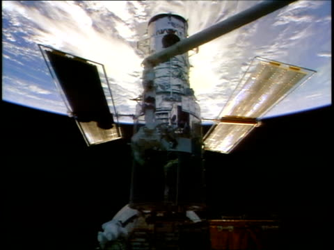 high angle astronauts smith lee doing repairs on hubble space telescope during eva / sts82 - sternenteleskop stock-videos und b-roll-filmmaterial