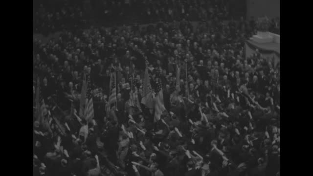 vidéos et rushes de high angle audience at madison square garden during rally of the german-american bund / pan right to follow flag corps bearing us and bund flags as... - nazism