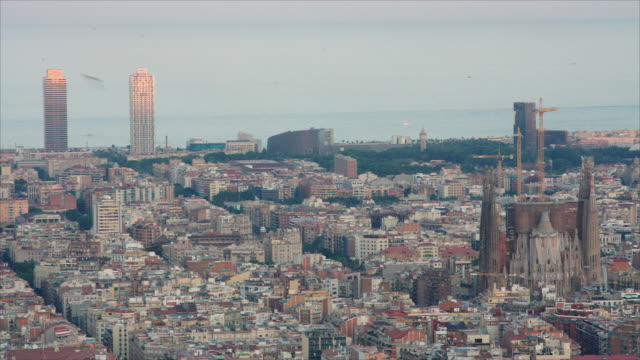 High angle Barcelona skyline at sunset. Wide shot from Horta Bunkers, the best viewpoint to overlook the city. We can see Sagrada Familia, Mapfre and Arts twin towers and the Mediterranean sea.