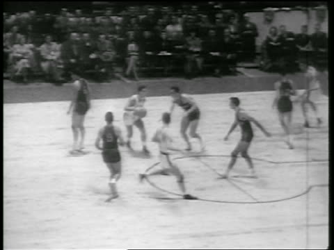 B/W 1946 high angle PAN basketball players blocking basket / Huskies vs Knicks / newsreel