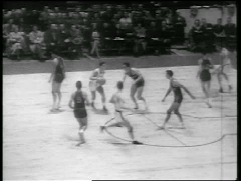 vídeos de stock, filmes e b-roll de b/w 1946 high angle pan basketball players blocking basket / huskies vs knicks / newsreel - 1946