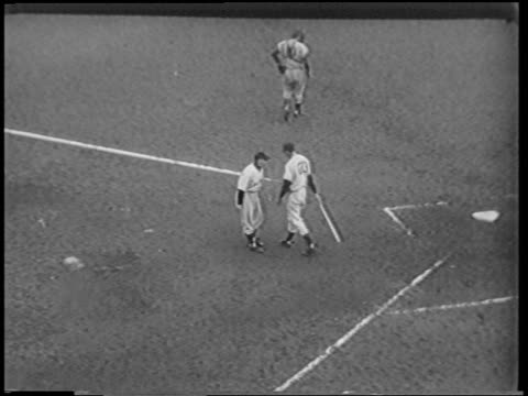vídeos de stock e filmes b-roll de b/w 1951 high angle batter talking to coach / coach hits him on buttocks / catcher walking / polo grounds - camisola de basebol