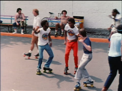 stockvideo's en b-roll-footage met 1978 high angle black + caucasian men on roller skates dancing in park / nyc / educational - archief