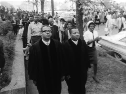 B/W 1963 high angle PAN Black clergy leading marchers in civil rights demonstration / Alabama / newsreel