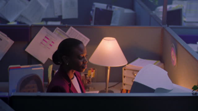 high angle black woman working at computer in cubicle with lamp on / other cubicles in dark office in background - 2000 stock videos and b-roll footage