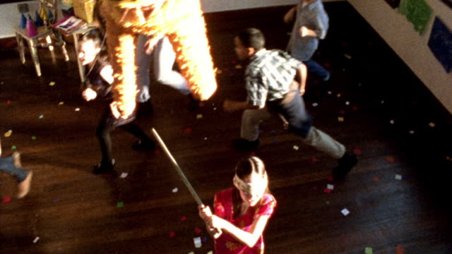 high contrast high angle blindfolded girl swinging stick at pinata in foreground / excited children run around her - papier stock videos & royalty-free footage
