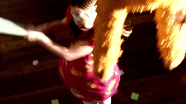 high contrast high angle ms blindfolded girl swinging stick at pinata in foreground + spinning around - high contrast stock videos & royalty-free footage