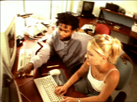 overexposed grainy high angle  blonde teen girl + young black man working on computer - 女子大生点の映像素材/bロール