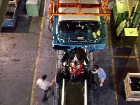 vídeos y material grabado en eventos de stock de 1959 high angle blue car body being lowered to men assembling car on assembly line below / 1960 chevy - fábrica de coches