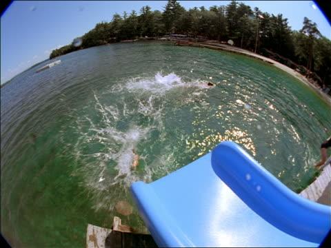 vídeos y material grabado en eventos de stock de fisheye high angle bottom of slide as girl slides on stomach into lake followed by boy sliding in lake - traje de baño de una pieza