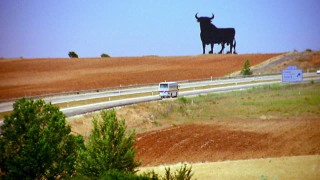 vídeos de stock e filmes b-roll de high angle bull statue on golden hillside with bus + car passing on highway in foreground / between madrid + seville - touro animal macho