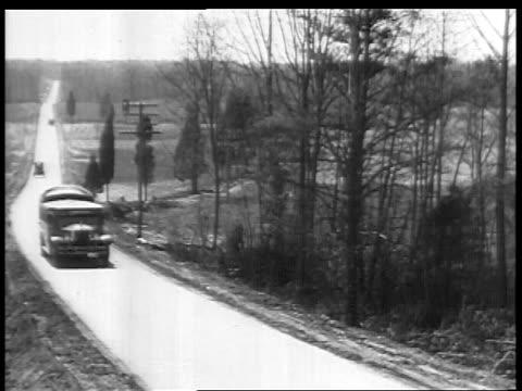 b/w 1927 high angle bus on country road / educational - 1927年点の映像素材/bロール