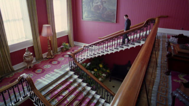 high angle businessman walking down grandiose pink staircase in Dublin Castle / Dublin, Ireland