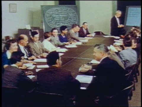 1957 high angle businessmen + women sit at table in conference room - 1957 stock videos & royalty-free footage
