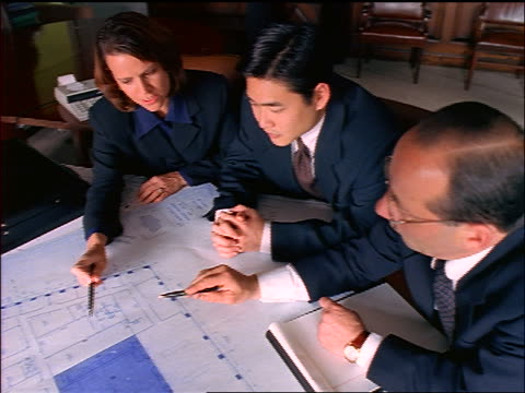 high angle businesswoman + two businessmen (one asian) discuss blueprints on table in conference room - femmina con gruppo di maschi video stock e b–roll