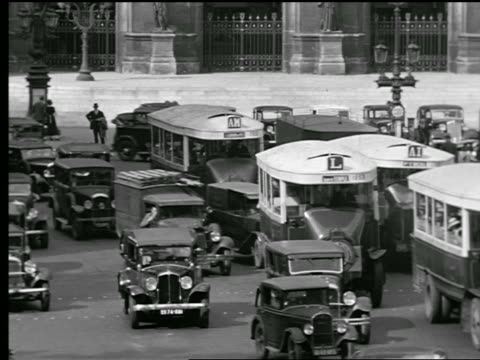 b/w 1927 high angle busy intersection with cars + buses moving slowly in place de l'opera / paris, france - place de l'opera stock videos and b-roll footage