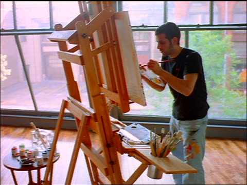 high angle canted pans gen x man painting at easel in loft - staffelei stock-videos und b-roll-filmmaterial
