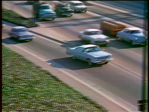 1959 high angle PAN car pulling off of on-ramp into heavy traffic on highway / Los Angeles / educational