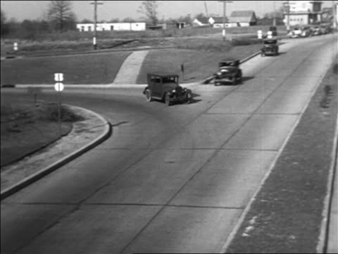 b/w 1934 high angle pan car pulling out into highway traffic + colliding with oncoming car / staged collisions - 1934 stock videos & royalty-free footage