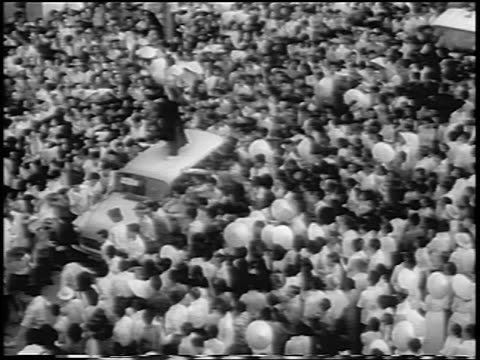 B/W 1963 high angle car with man on roof moving thru crowd at Buddhist protest / South Vietnam / newsreel
