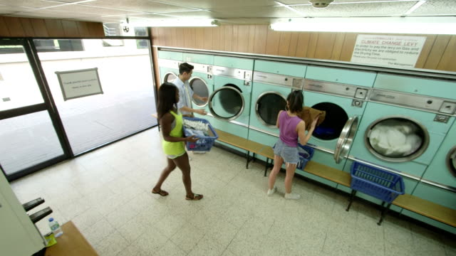 high angle ls cctv style three young adults use the launderette - launderette stock videos and b-roll footage