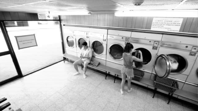 High Angle LS CCTV Style Three Young Adults use the Launderette