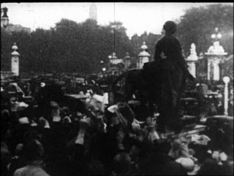 b/w 1938 high angle pan cheerinc crowd in front of buckingham palace gates / after signing of munich pact - anno 1938 video stock e b–roll