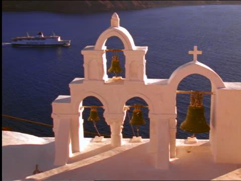 stockvideo's en b-roll-footage met high angle church bell towers overlooking ferry moving across sea / santorini, greece - kleine groep dingen